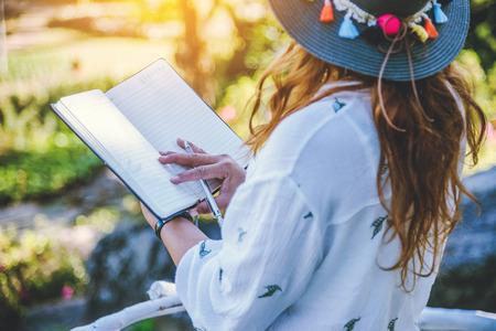 Aziatische vrouw reizen aard. Reis ontspannen. Studeer, lees een boek. Natuureducatie Schrijf een notitie Op openbaar park in de zomer. In Thailand