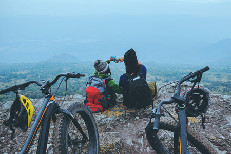 Asian lover woman and man Travel Nature. Travel relax ride Mountain Bike in the wild. Sit down on a rocky cliff. Thailand