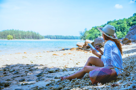 Asian woman travel nature. Travel relax. Study read a book. Nature Education Write a note. On the beach. In the summer. Thailand