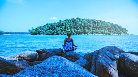 Asian woman relax in the holiday. Travel relax.  Play if yoga. On the rocks by the sea. In the summer. Thailand