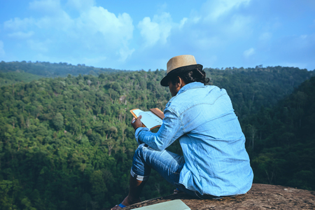 Asian man travel relax in the holiday. seats relax read books on rocky cliffs. On the Moutain summer. In Thailand