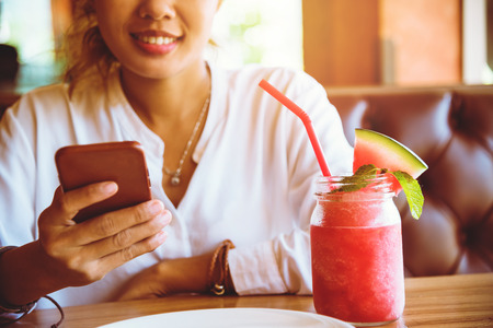 Asian woman sit back and relax drink fruit. And the phone is holding. 스톡 콘텐츠