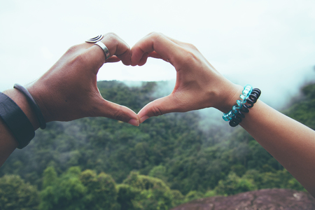 Asian lover couple woman and man travel nature. hand heart-shaped. With nature on the mountain with fog Stok Fotoğraf
