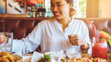 Asian woman sitting eat food happily. at restaurant