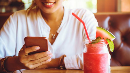 Asian woman sit back and relax drink fruit. And the phone is holding. Stockfoto