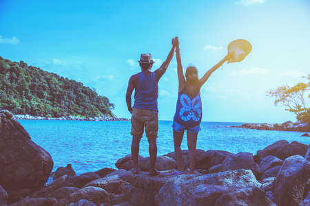 Asian lover couple women and men travel nature. Travel relax. Play sea water on the beach. In the summer. Thailand 스톡 콘텐츠