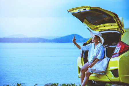 Asian woman travel nature. Travel relax. Sitting on the car at the beach.