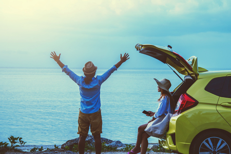 Asian lover couple woman and man travel nature. Travel relax. Sitting on the car at the beach. In the summer