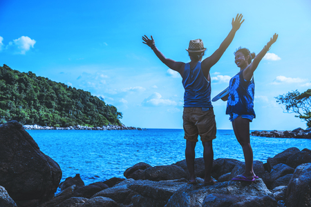 Asian lover woman and man travel nature. Travel relax. On the rocks at the sea. In the summer. Thailand Stock Photo