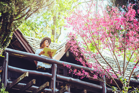 Asian woman travel nature. Travel relax. Standing reading book the balcony of the house. in summer.