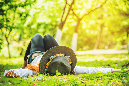 Asian woman travel nature. Travel relax. sleep on the lawn in the park. in summer. Stock Photo