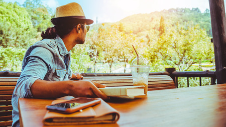 Asian man travel nature. Travel relax. read books and drink coffee. In the coffee shop. Stockfoto