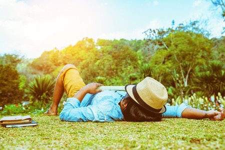 Asian man travel nature. Travel relax. sleep on the lawn in the park. in summer. Stock Photo