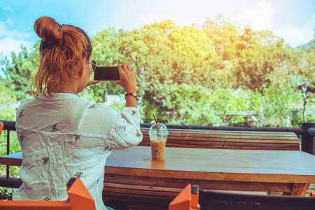 Asian woman travel nature. Travel relax. Hands are holding the phone. In the coffee shop.