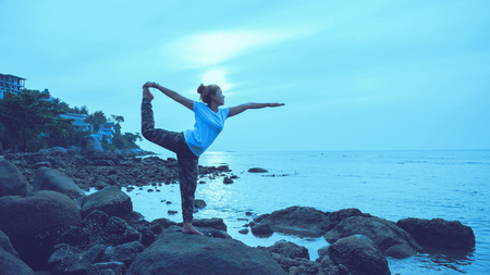 Asian woman travel relax in the holiday. Play if yoga. On the rocks by the sea.