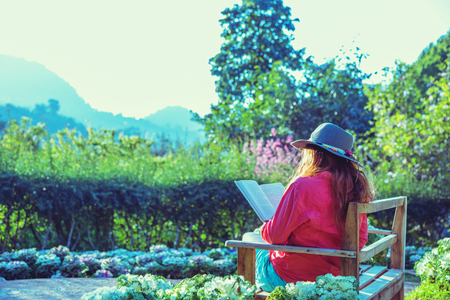 Asian woman travel nature. Travel relax. Read the book on the bench in the park in summer.