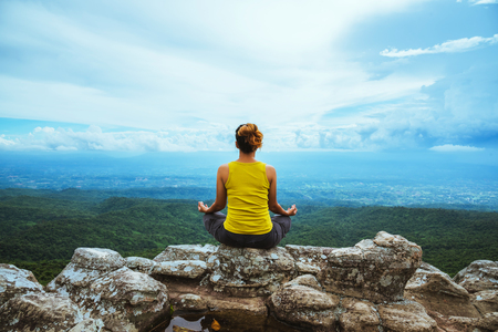 Asian woman relax in the holiday. Travel relax.  Play if yoga. On the Moutain rock cliff. Nature of mountain forests in Thailand