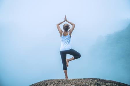 Asian woman relax in the holiday. Play if yoga. On the Moutain rock cliff Stock Photo