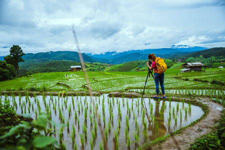 Asian woman travel nature. Travel relax. Walking take a photo on the field. in summer.