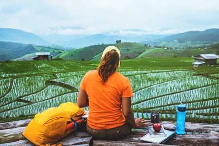 Asian woman travel nature. Travel relax. sit reading book the balcony of the resort. View of the field on the Moutain in summer. Thailand Stok Fotoğraf