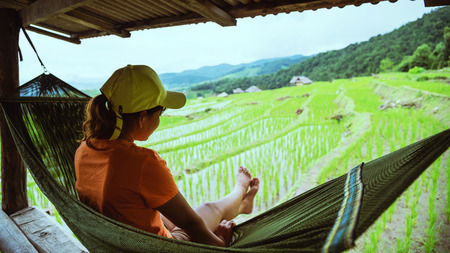Asian woman travel nature. Travel relax. Relax in the hammock the balcony of the resort. View of the field on the Moutain in summer. Thailand