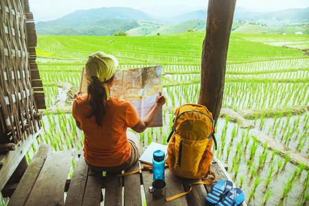 Natura di viaggio donna asiatica. Viaggia rilassati. sit guarda la mappa il balcone del resort. Vista del campo in montagna in estate. Tailandia Archivio Fotografico