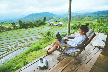 Asian woman travel nature. Travel relax. sit work with a laptop the balcony of the resort. View of the field on the Moutain in summer. Thailand