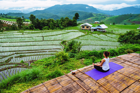 Asian woman relax in the holiday. Play if yoga. On the balcony landscape Natural Field 写真素材