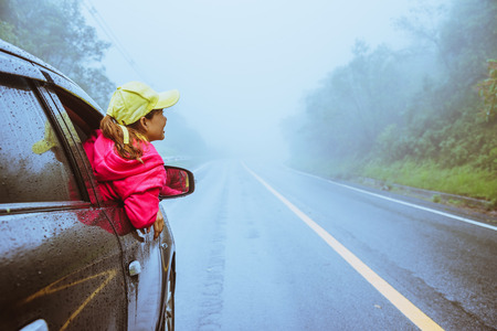 Asian women travel relax in the holiday. driving a car traveling happily. Amid the mist  rainy.