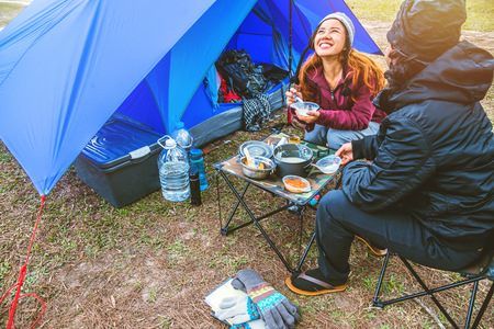 Lover women and men asians travel relax camping in the holiday. camping on the Mountain. sit eat breakfast. Thailand Standard-Bild