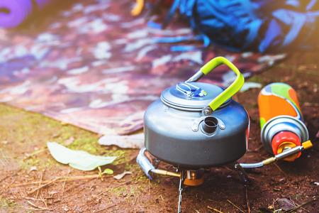 acampar en la montaña. hervidor colocado sobre una estufa de gas para picnic.