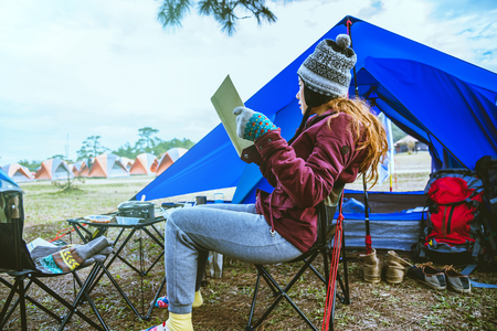 Asian woman travel relax camping in the holiday. camping on the Mountain. sit relax read a book In the chair. Thailand