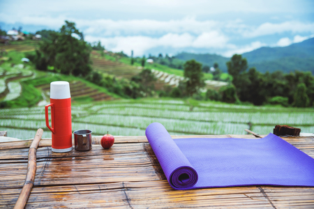 Purple yoga mat and red water bottle with a glass of water stainless Put forward. And Red apple on wooden background. On the balcony landscape Natural Field.Travel relax. papongpieng in Thailand 版權商用圖片