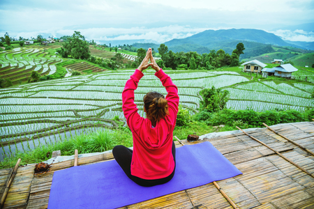 Asian woman relax in the holiday. Play if yoga. On the balcony landscape Natural Field.papongpieng in Thailand