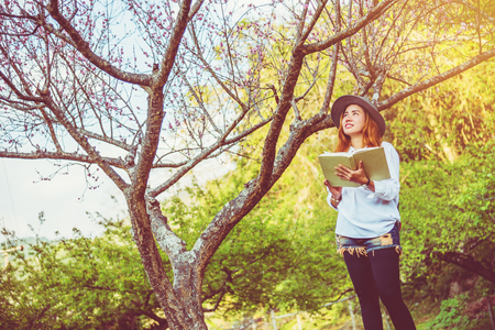 Asian woman travel nature. Travel relax. Reading book On the in the park. in summer. Stock Photo