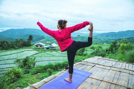 Mujer asiática relajarse en las vacaciones. Juega si yoga. En el balcón paisaje Natural Field.papongpieng en Tailandia Foto de archivo