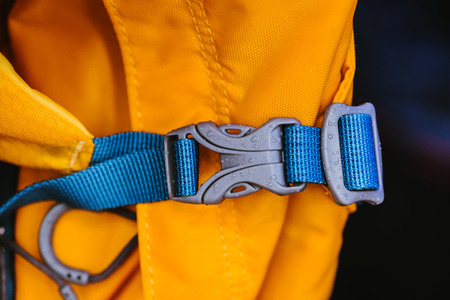 Close-up detail of locked blue convenient plastic clasp of backpack yellow.