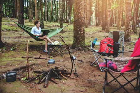 Asian women travel natural relax . Sitting working using a notebook. in the hammock. campsite on the national park  Doi inthanon at Chiangmai. in Thailand