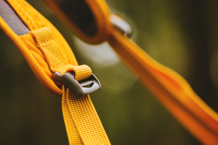Close-up detail of locked black convenient plastic clasp of backpack yellow.