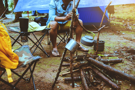 Asian man relax travel nature in the holiday. camping and Boil water drink coffee on the doi inthanon. at Chiangmai in Thailand. 写真素材