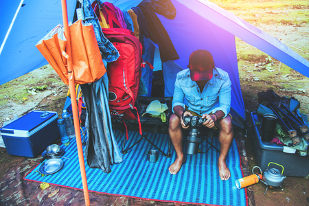 Asian man relax travel nature in the holiday.Take a picture Nature Study in the Jungle camping on the Mountain. rainy season at Chiangmai in Thailand.