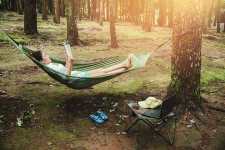 Les voyages naturels des femmes asiatiques se détendent pendant les vacances. dormir en lisant un livre dans le hamac. camping sur le parc national Doi inthanon à Chiangmai. en Thaïlande Banque d'images