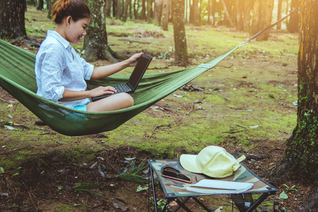 Women travel in natural sitting in the hammock and working in a natural park using a notebook.