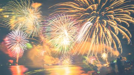 Fuegos artificiales con siluetas de personas en eventos de vacaciones. Fuegos artificiales de año nuevo en la playa.