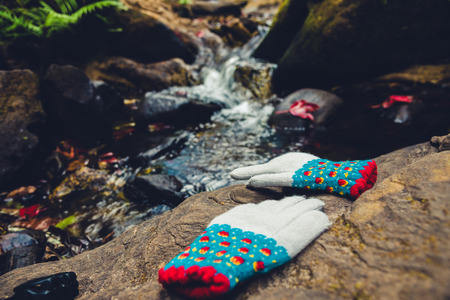Natural background. Maple leaves on the rocks at the waterfall. Winter gloves placed on the stone. Imagens