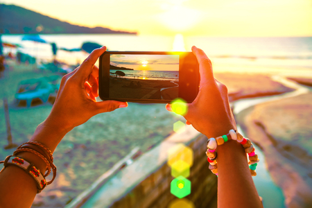Asian woman travel nature. Travel relax. Use cell phone take pictures the sunset on the beach. In the summer