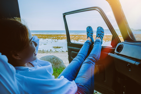 Asian woman travel nature. Travel relax at the beach in the summer. Sitting in the car Happy to see the sea and Leg outside the car.