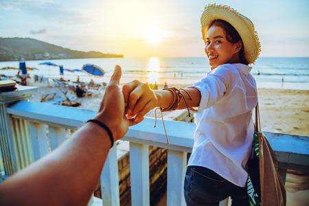 Amantes asiáticos felices y sonríen tomados de la mano. Viaje de vacaciones de verano en la playa.