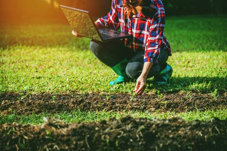 Mujer joven con portátil sentado en parcelas huerta. usando tecnología agrícola usando datos de análisis de computadora tableta leer un informe.