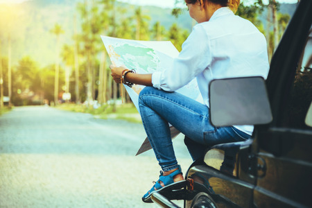 woman travel relaxing nature mountain map navigation. Sit on the car and browse the map.